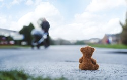 Rear view Lonely Teddy bear doll sitting alone on hailstones with blurry father pushing stroller walking on footpath.lost brown bear toy looking out on the road, International missing children's day
