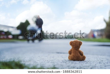 Rear view Lonely Teddy bear doll sitting alone on hailstones with blurry father pushing stroller walking on footpath.lost brown bear toy looking out on the road, International missing children's day Photo stock ©