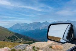 Rear view mirror of a car stopped at a scenic overlook along Trail Ridge Road in Rocky Mountain National Park