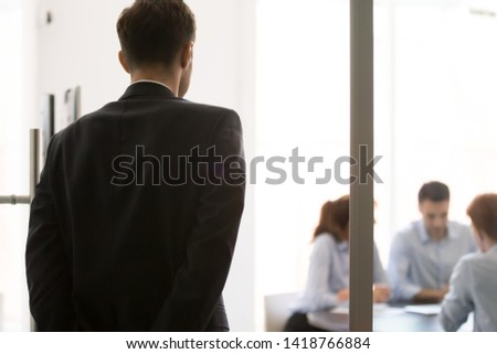 Rear view nervous man standing near glass door waiting looking at participants sitting at desk at business meeting. Lack self-confidence, public speaking fear, stressed applicant before job interview #1418766884