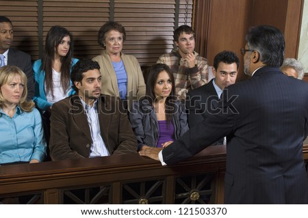 Rear view of a advocate communicating with the jurors in the court house