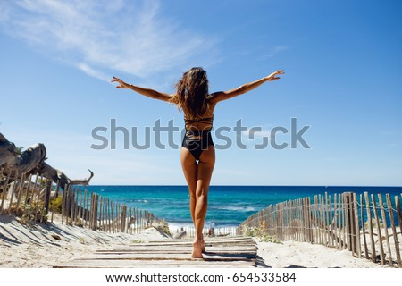 Rear view of a beautiful, brunette young girl with raised hands, looking at ocean. Freedom concept, holiday, beach, clear sky background. Corsica island, France. Horizontal view. #654533584