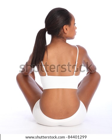 Rear view of a beautiful healthy young african american woman wearing white sports underwear, sitting cross legged against white background showing off fit body.