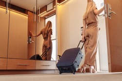 Rear view of a beautiful slim young woman in brown stylish overalls with suitcase leaves the hotel room after long therapeutic vacation. Young business woman goes on a business trip leaving her house