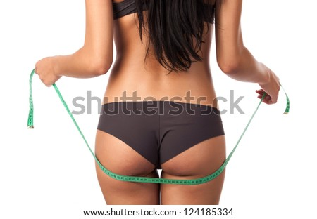 Rear view of a beautiful young woman holding a measure tape