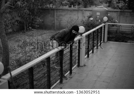 Rear View Of A Burglar Entering In A House Stockfoto ©