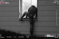 Rear View Of A Burglar Entering In A House Through A Open Window