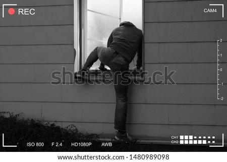 Rear View Of A Burglar Entering In A House Through A Open Window Stockfoto ©