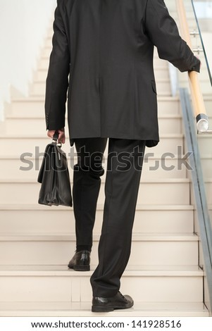Rear view of a business entrepreneur ascending the staircase