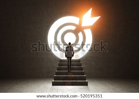 Rear view of a businessman climbing stairs. Large target on the wall is glowing with orange light. Toned image