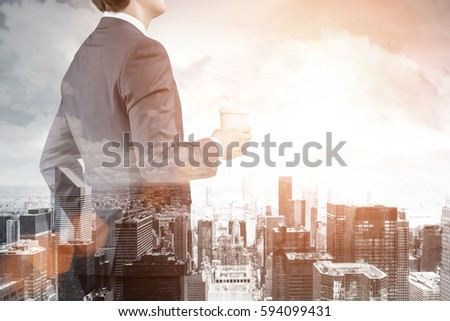 Rear view of a businessman holding his paper cup of coffee and looking at the urban panorama. There is a cityscape in the background. Toned image. Double exposure. #594099431