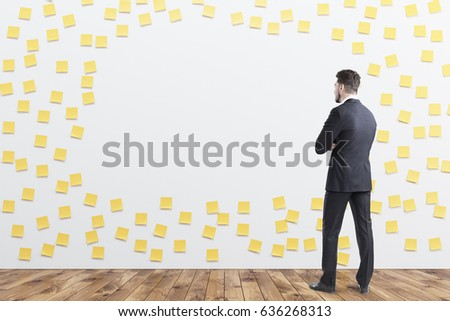 Rear view of a businessman in gray looking at a wall covered by yellow sticky notes and a blank piece. 3d rendering, mock up