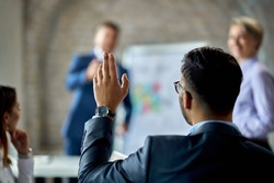 Rear view of a businessman raising his hand to ask the question during business presentation in the office.