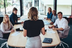 Rear view of a businesswoman addressing a meeting in office. Female manager having a meeting with her team in office boardroom.