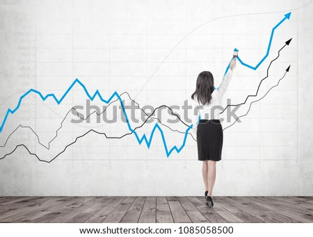 Rear view of a businesswoman wearing a black skirt and a white blouse drawing with a paintbrush. Gray and blue growing graphs drawn on a concrete wall #1085058500