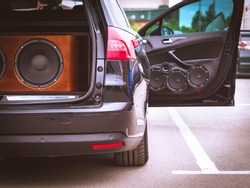 Rear View of a Car, Trunk and Front Door Open, With Installed Car Audio System, Sound Speakers and Giant Subwoofer Sound Speaker.