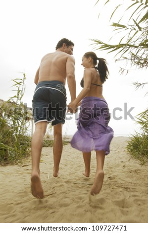 Rear view of a cheerful couple running together while holding hands on beach - stock photo