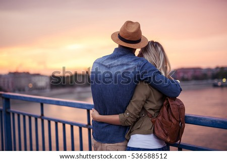 Rear view of a couple cuddling and enjoying sunset together. #536588512
