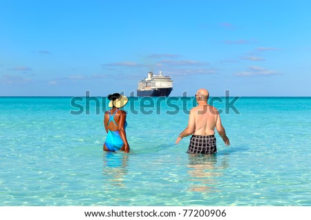 Rear view of a couple walking on the beach and watching cruise ship