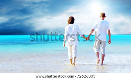 Rear view of a couple walking on the beach, holding hands.