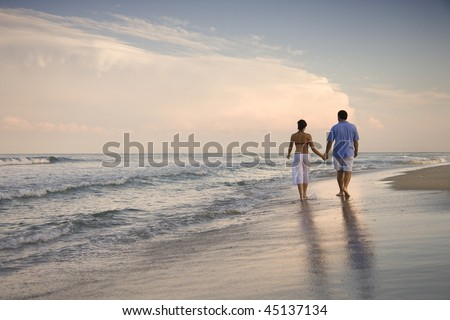 Rear view of a couple walking on the beach, holding hands. Horizontal shot. - stock photo