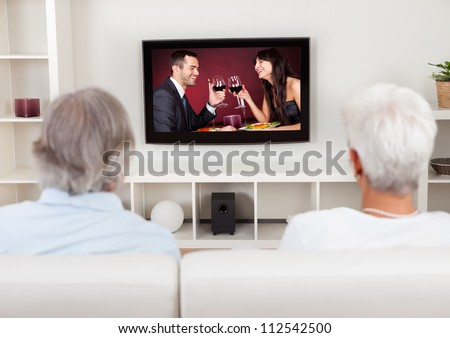 Rear view of a couple watching television with a scene on the screen of a young man and woman celebrating