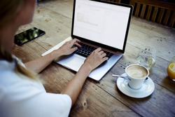Rear view of a creative female freelancer sitting front laptop computer with blank copy space screen for your information, young business woman work on net-book during breakfast in coffee modern shop