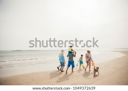 Rear view of a family walking along the beach with their dog while on holiday.