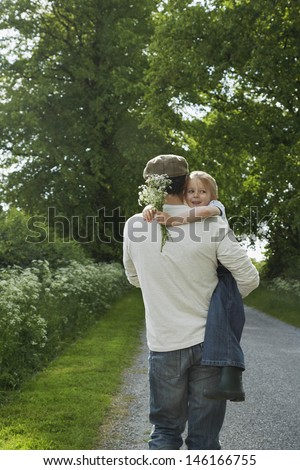 Rear view of a father carrying daughter with flowers on country lane