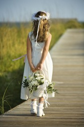 Rear view of a flower girl walking on a boardwalk holding a flower basket behind her back. Vertical shot.