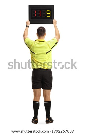 Rear view of a football referee holding a substitute board isolated on white background
