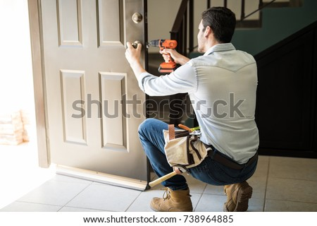 Rear view of a good looking man working as handyman and fixing a door lock in a house entrance