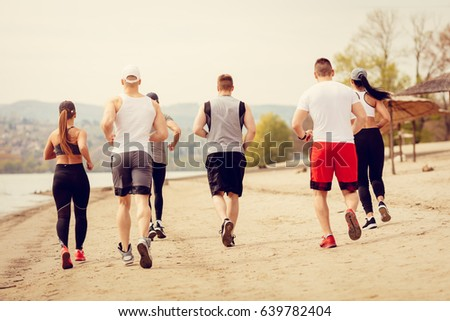 Rear view of a group young friends running together on the beach. #639782404