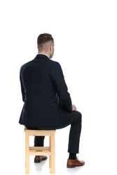 Rear view of a handsome businessman sitting on a chair on white studio background