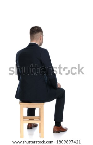 Rear view of a handsome businessman sitting on a chair on white studio background ストックフォト ©