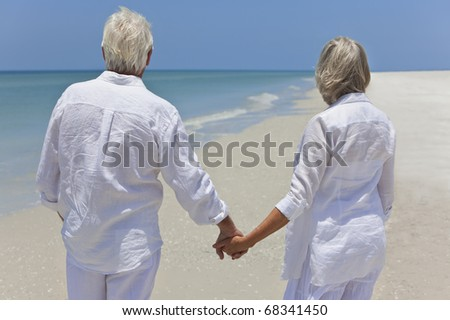Rear view of a happy senior man and woman couple together holding hands and looking out to sea on a deserted tropical beach with bright clear blue sky