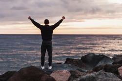 Rear view of a happy unidentified man athlete rejoices in a fulfilled dream by raising his hands up and looking at sunset by the sea on warm summer evening. Concept of achieving goals and results