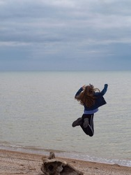 Rear view of a jumping girl on the beach. A happy teenage girl in clothes pretends to fly into the water. The concept of freedom, independence and a quick holiday break. Space for your text.