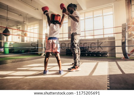Rear view of a kid standing inside a boxing ring with raised hands along with his trainer. Trainer raising the hand of a boxing kid standing inside a boxing ring.