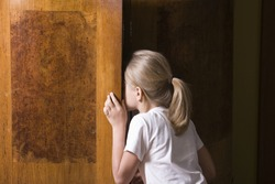Rear view of a little girl opening wardrobe door