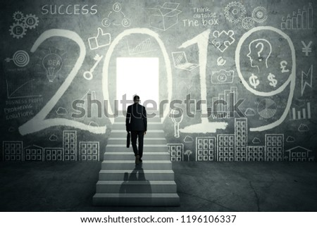 Rear view of a male entrepreneur holding a suitcase on the stair while walking toward a bright door with numbers 2019 and doodles