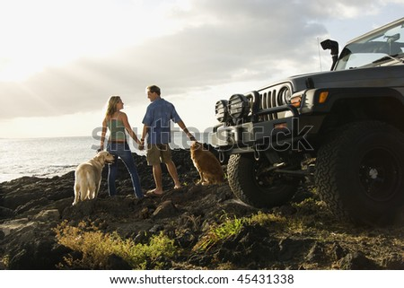 Rear view of a man and woman holding hands and relaxing with their dogs at a beach with the edge of an SUV visible in the foreground. Horizontal format.