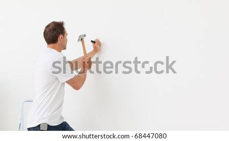 Rear view of a man hammering against a white wall standing on a ladder