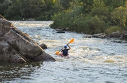 Rear view of a man rafting with kayak on a fast watercourse passing through cliffs and forested areas