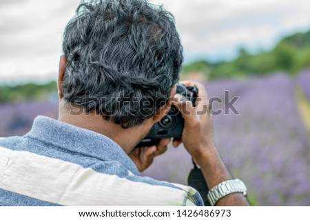 Rear view of a man taking picture of a lavender field