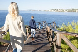 Rear view of a mother and son walking together towards the sea on a wooden deck on a sunny holiday, nature outdoors. Tourist family visiting a destination beach, travel recreation lifestyle, exterior