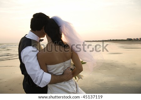 Rear view of a newlywed couple hugging on beach. Horizontal shot.