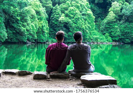 rear view of a romantic gay couple sitting in a beautiful landscape with lake and mountains in a calm moment Stockfoto ©