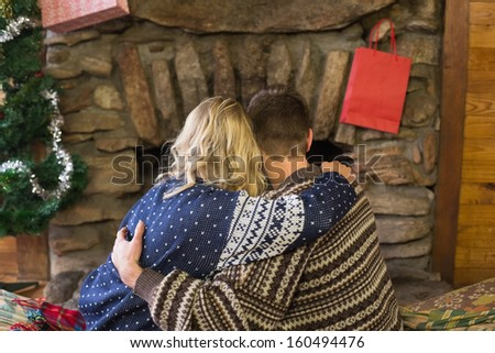 Rear view of a romantic young couple embracing in front of fireplace #160494476