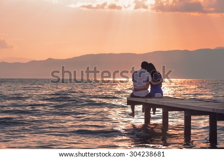 Rear view of a romantic young couple sitting on the pier enjoying  stunning sunset